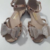 Sandalia dourada de laço